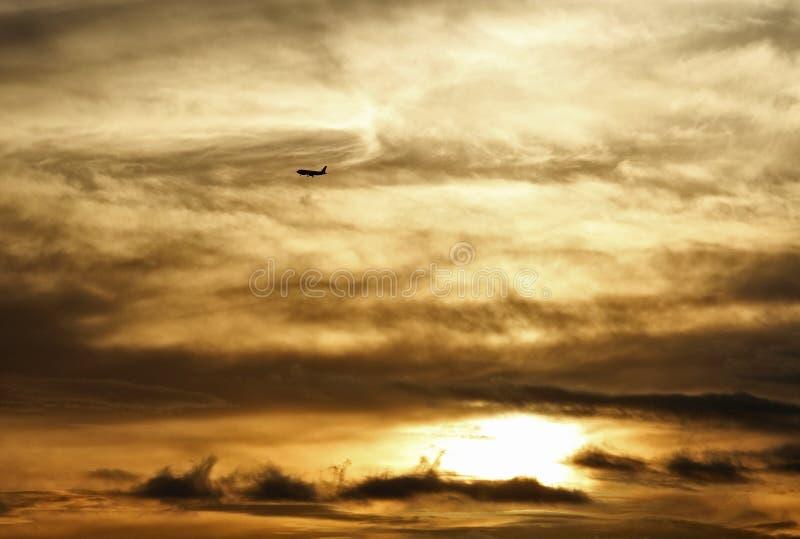 Płaski latanie nad chmurami w złotym zmierzchu zdjęcia stock
