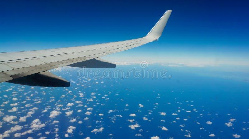 Płaski skrzydło nad pięknym oceanem dostrzegającym z chmurami zdjęcia royalty free