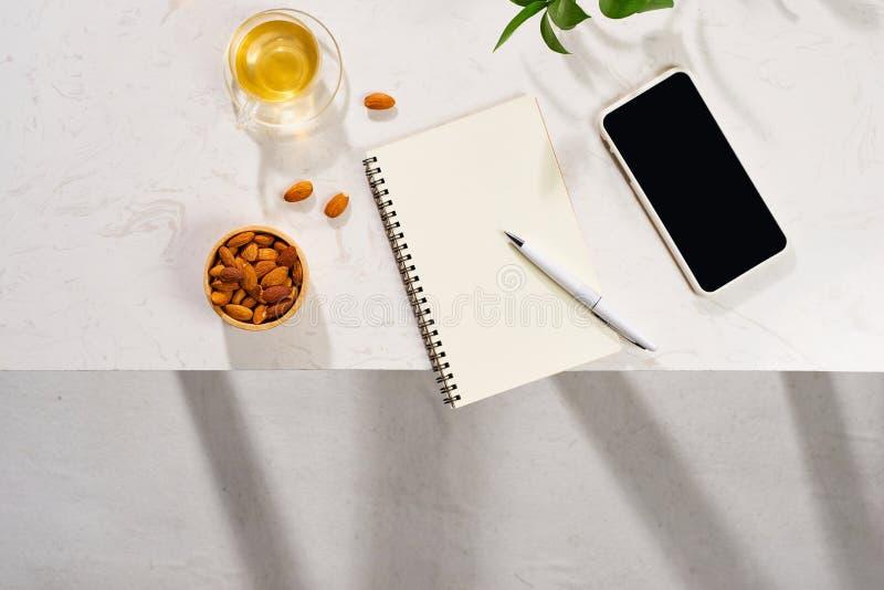 Płaski telefon komórkowy, smartfon, makaron z ciasta, filiżanka herbaty, migdały, notebook i pióro na białym tle Widok z góry obraz royalty free
