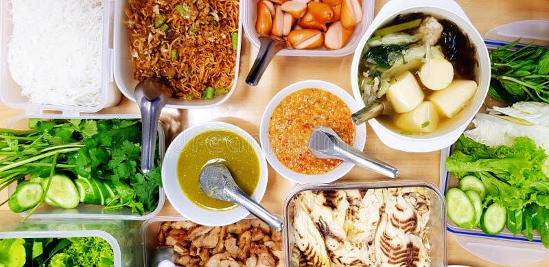 Płaskie jedzenie na obiad z kawałkami ryb, świeżych warzyw, zupy, kiełbasy i sos przyprawy na drewnianym stole obraz stock