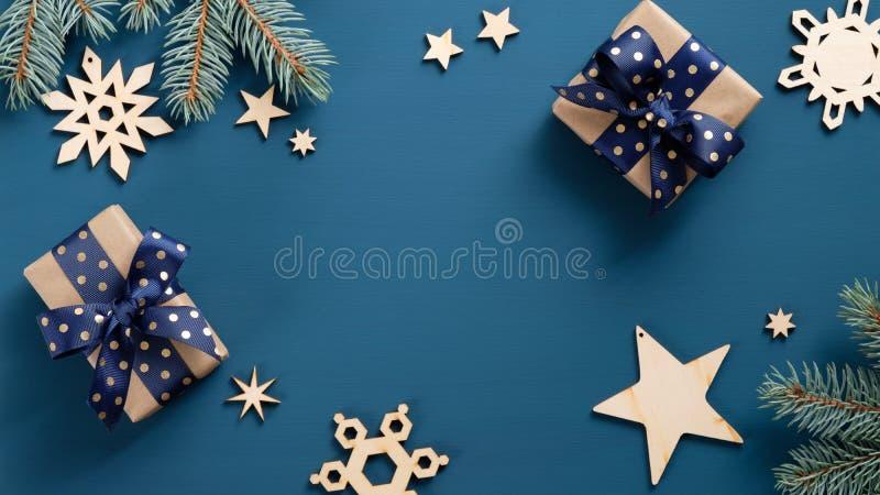 Płaskie pudełka na prezent świąteczny i gałęzie jodły z drewnianymi ozdobami wykonanymi ręcznie na ciemnoniebieskim tle Ramka świ obraz stock