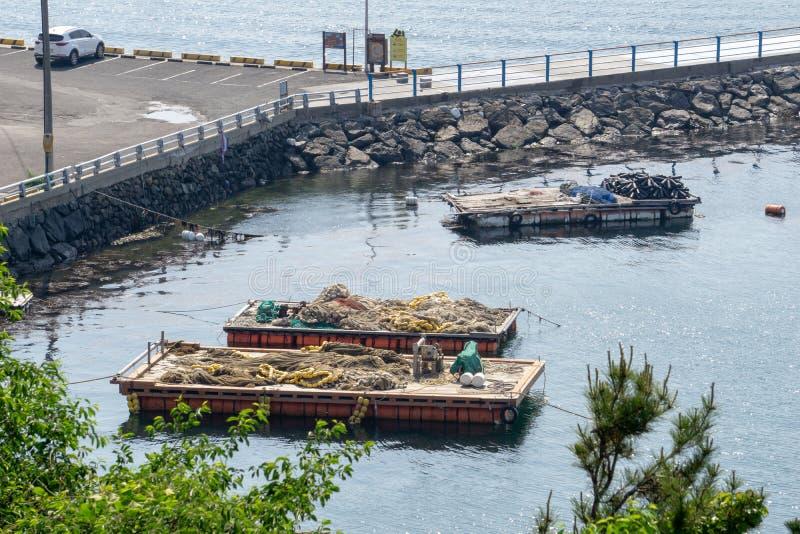 Płaskiego wierzchołka ponton z pociesza i sieci na pokładzie cumują przy brzeg blisko Samsung przemysłów ciężkich lub SHI obraz stock