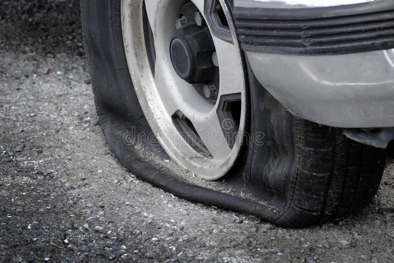 Płaskiej opony pojazdu samochód na Drogowy niebezpieczeństwa Niebezpiecznym Splatającym zdjęcia royalty free