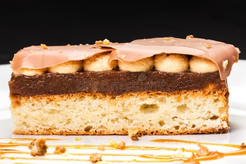 Płatowaty deser z karmelem, dokrętkami i czekoladą na bielu talerzu, obrazy stock