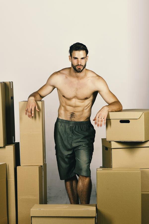 Płciowość i chodzenie w pojęciu: seksowny mężczyzna wśród pudełek zdjęcie stock