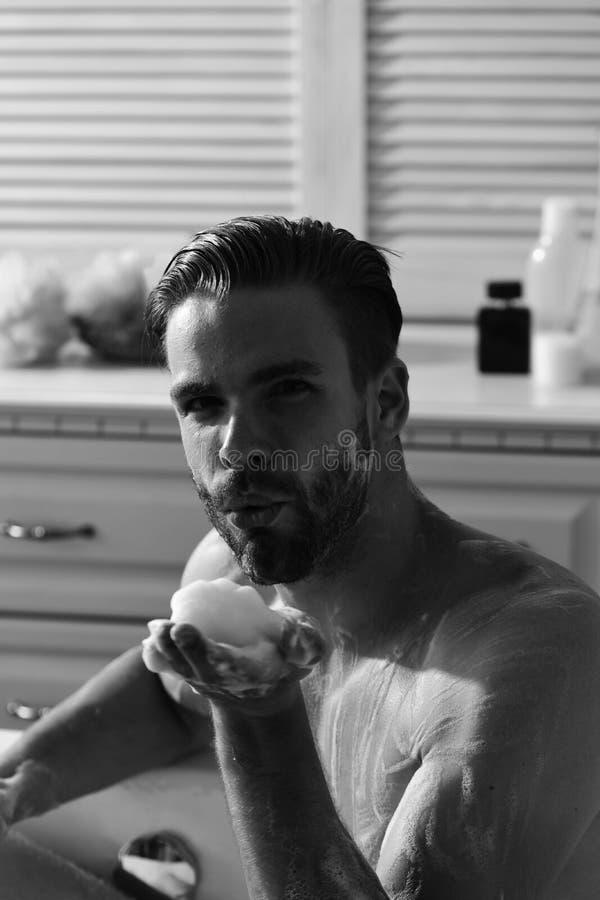 Płeć i erotyki pojęcie Mężczyzna z brodą i uwodzicielski twarzy dmuchanie pienimy się od palmy Mężczyzna z brodą i uwodzicielską  obraz royalty free