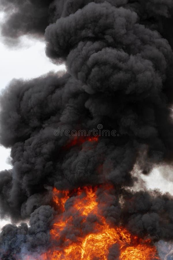 Płomienie czerwonego ogienia i ruchu chmury czerń dym zakrywali niebo zdjęcie royalty free