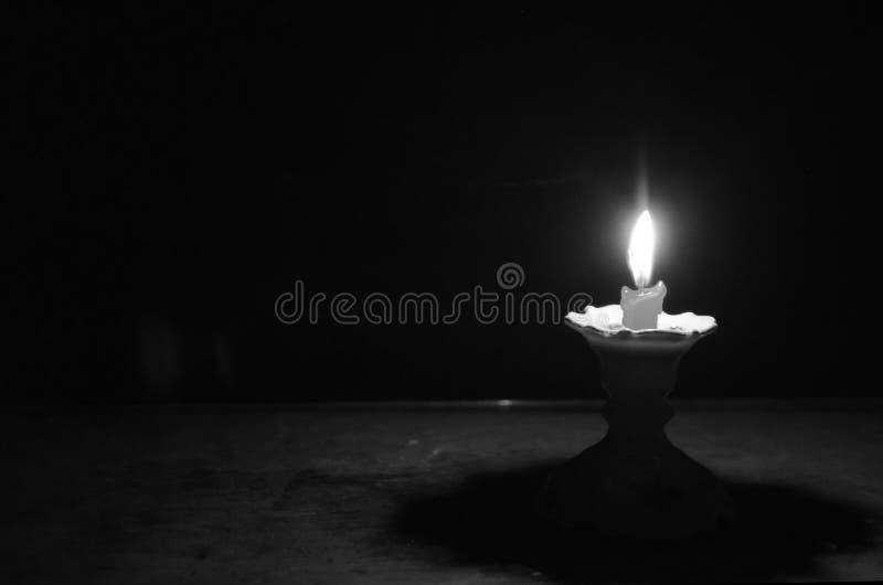 Płonąć lekki krótka świeczka na candlestick w zmroku obrazy royalty free