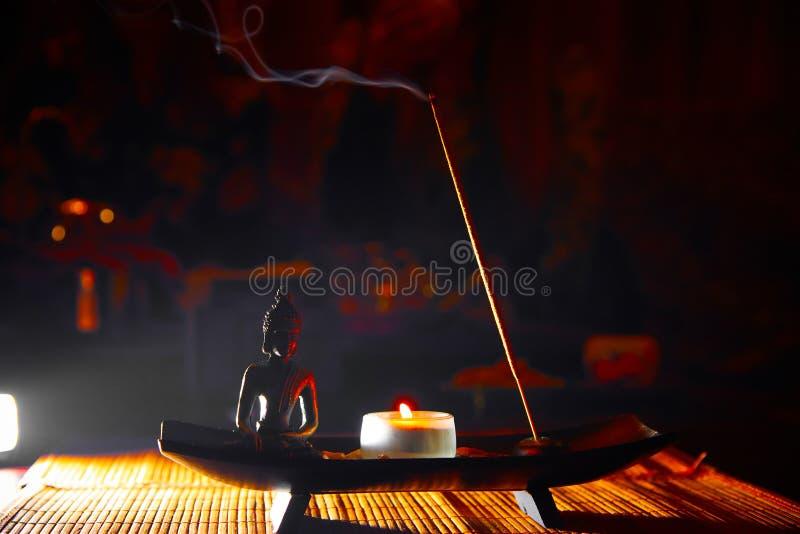 Płonąca świeczka i fragrant kij z dymem w ciemnym backlight zdjęcie stock