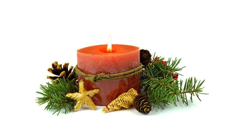 Płonąca świeczka, jodła, rożki, słomiane zabawki, dekoracyjne czerwone jagody obraz royalty free
