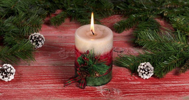 Płonąca świeczka na nieociosanych czerwonych drewnianych deskach z Bożenarodzeniowymi decorami obraz royalty free