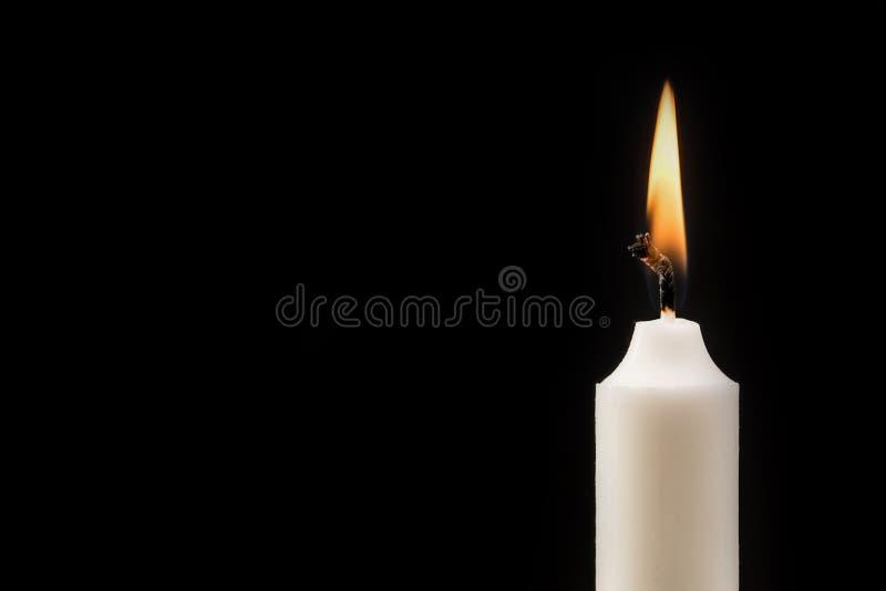 Płonąca świeczka przed czarnym tłem obraz royalty free