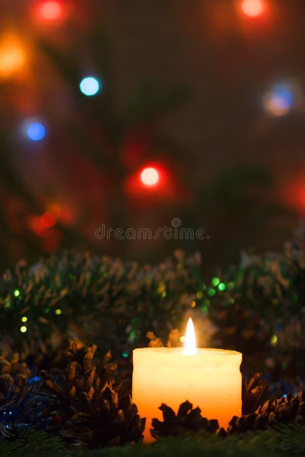 Płonąca świeczka wokoło sosnowych rożków fotografia stock