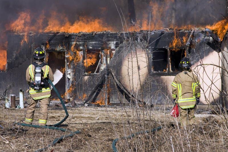 płonąca strażaków przodu domu pozycja obrazy stock