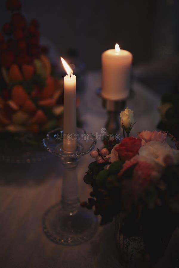 Płonące świeczki na brązowym candlestick przeciw ciemnemu tłu w domu ?wieczki w wn?trzu ilustracyjny lelui czerwieni stylu roczni zdjęcie royalty free
