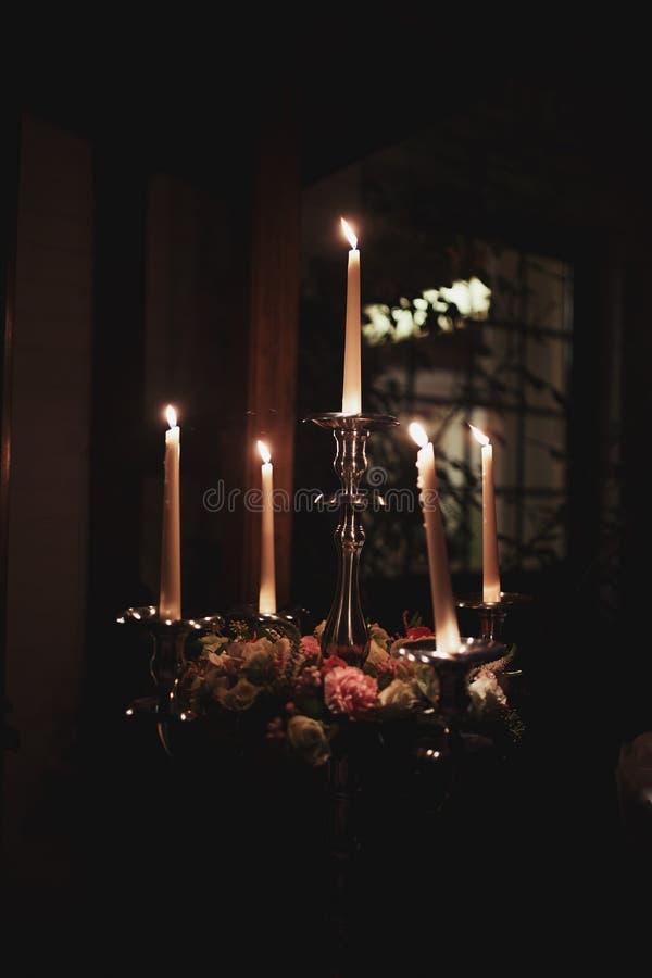 Płonące świeczki na brązowym candlestick przeciw ciemnemu tłu w domu ?wieczki w wn?trzu ilustracyjny lelui czerwieni stylu roczni obrazy royalty free
