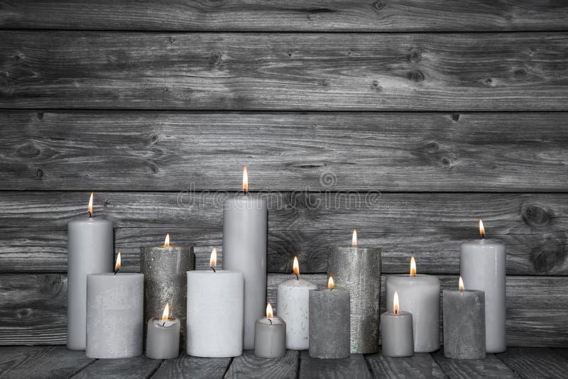 Płonące świeczki w bielu i siwieją na drewnianym podławym modnym backgrou zdjęcia stock