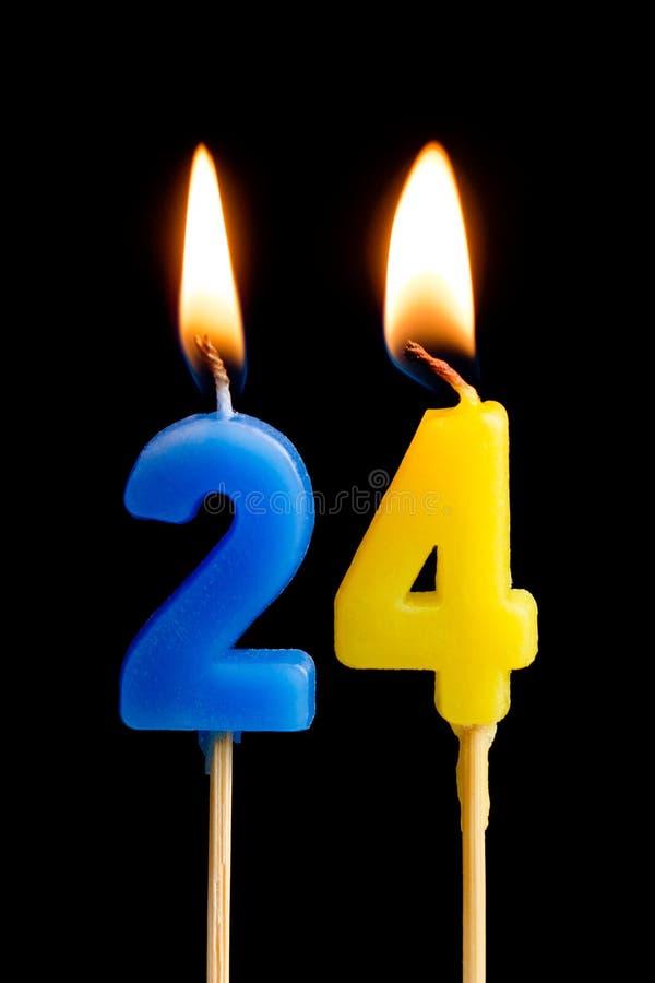 Płonące świeczki w postaci 24 dwadzieścia cztery liczby, daty dla torta odizolowywającego na czarnym tle Pojęcie świętować a zdjęcie royalty free