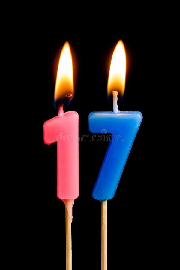 Płonące świeczki w postaci 17 siedemnaście postaci liczb, daty dla torta odizolowywającego na czarnym tle Pojęcie celebra zdjęcia royalty free