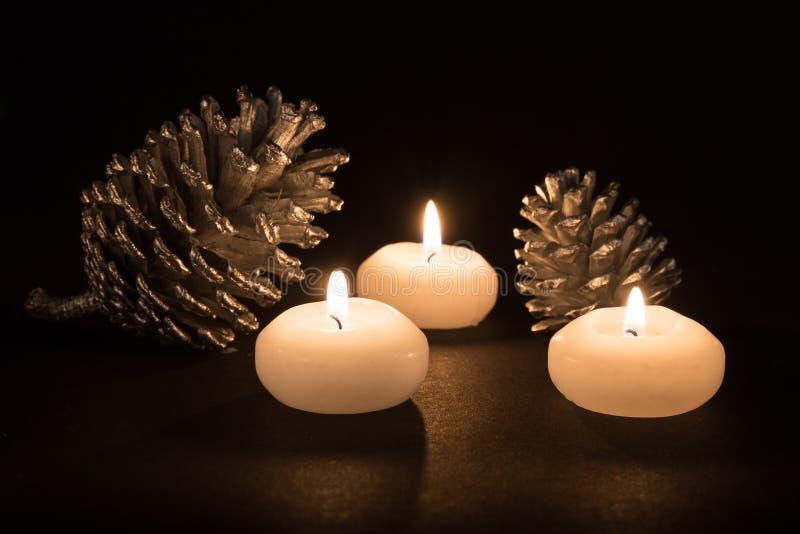 Płonące świeczki z sosnowymi jabłkami przy czarnym tłem obrazy royalty free
