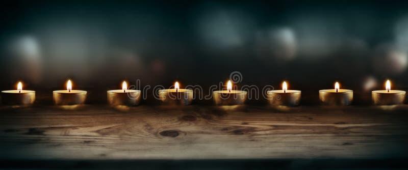 Płonące świeczki z zmrokiem - błękitny tło obrazy stock