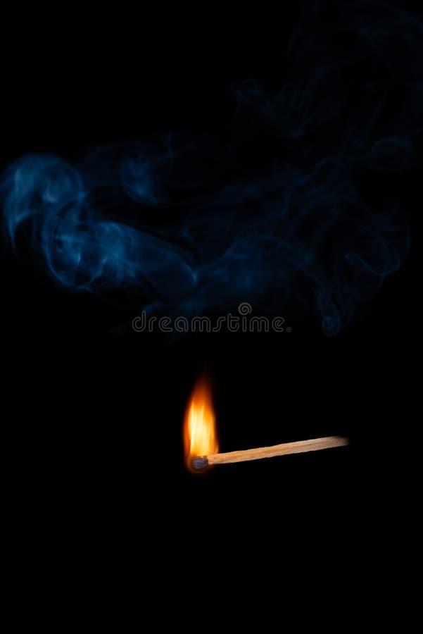 Płonący drewniany dopasowanie z błękita dymem nad czarnym tłem kosmos kopii zdjęcia stock
