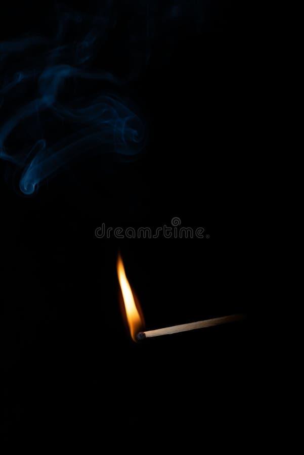 Płonący drewniany dopasowanie z błękita dymem nad czarnym tłem kosmos kopii fotografia stock