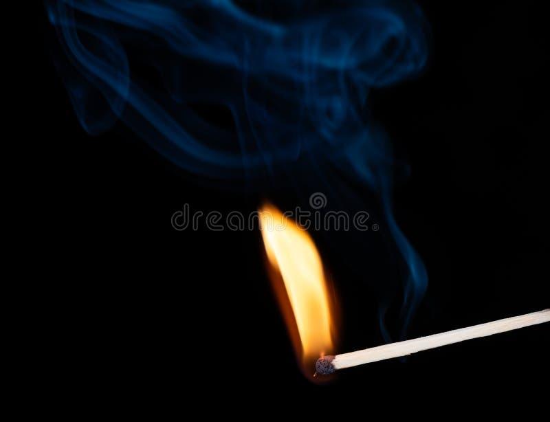 Płonący drewniany dopasowanie z dymem nad czarnym tłem kosmos kopii zdjęcie royalty free