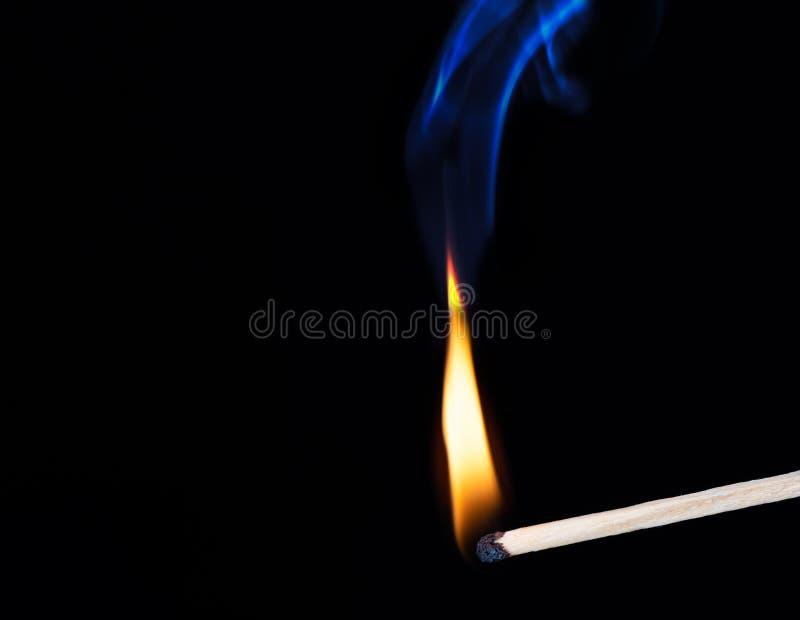 Płonący drewniany dopasowanie z dymem nad czarnym tłem obraz stock