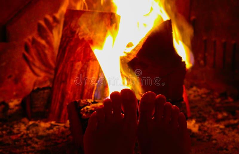 Płonący drewno przy grabą, żeńskie nogi jest rozgrzewkowy up Firewo zdjęcie royalty free