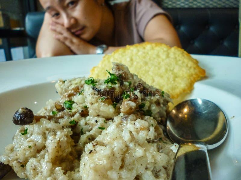 Płytka jedzenia zrobiona z ryżu, grzybów i mięsa przed kobietą w tle, tracąca apetyt obrazy stock