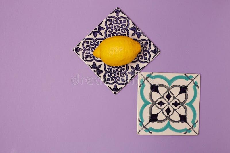 Płytki ceramiczne z ozdobą na fioletowym tle i soczystymi cytrynami, widok z góry obraz stock