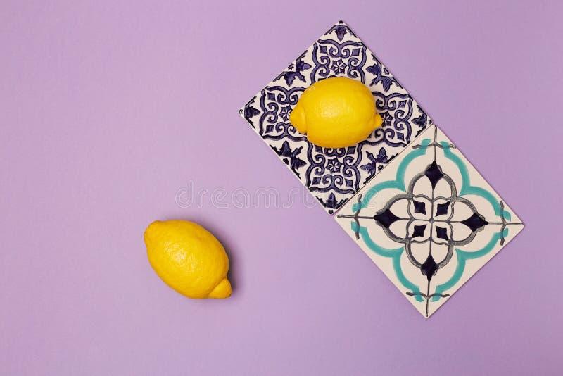 Płytki ceramiczne z ozdobą na fioletowym tle i soczystymi cytrynami, widok z góry zdjęcie royalty free