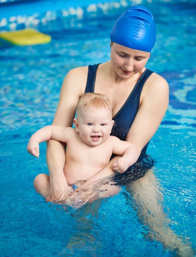 Pływać dla niemowlaków Portret patrzeje roześmianego dziecka w ona potomstwo matka ręki Mamy dopłynięcie z dzieckiem w basenie fotografia royalty free