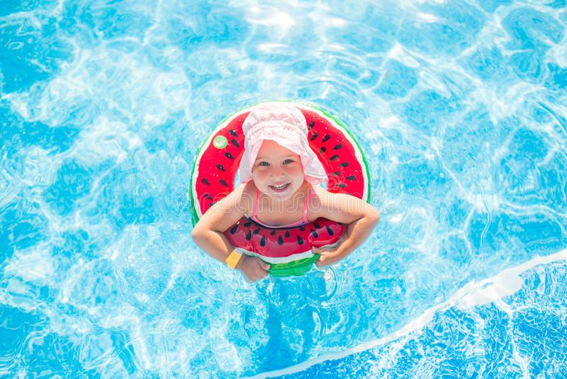 Pływać, wakacje - urocza uśmiechnięta dziewczyna w różowym kapeluszu bawić się w błękitne wody z arbuzem obrazy stock