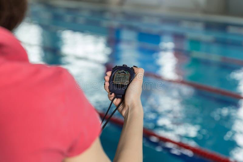 Pływacki powozowy mienia stopwatch poolside przy czasu wolnego centrum obrazy royalty free