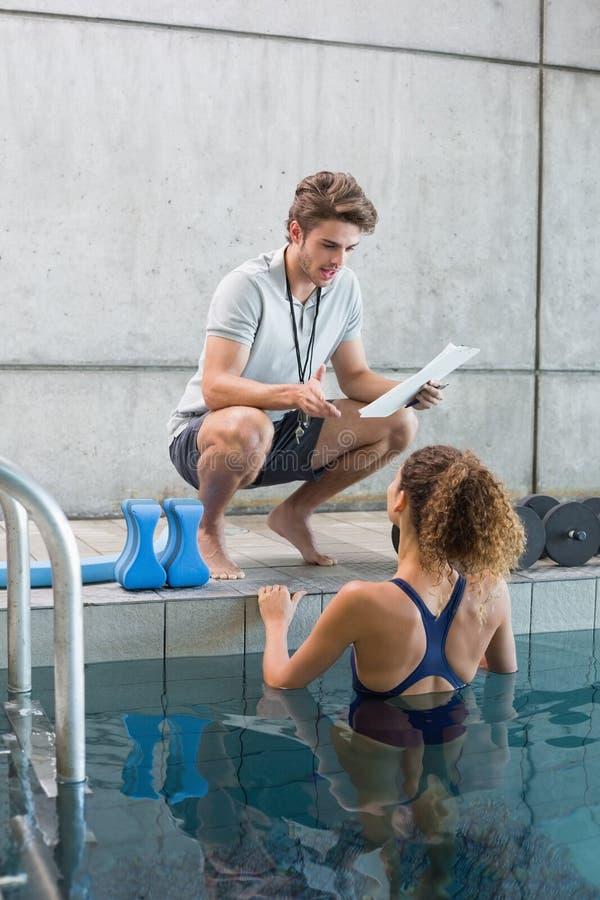 Pływaczka opowiada jej powozowy poolside fotografia stock