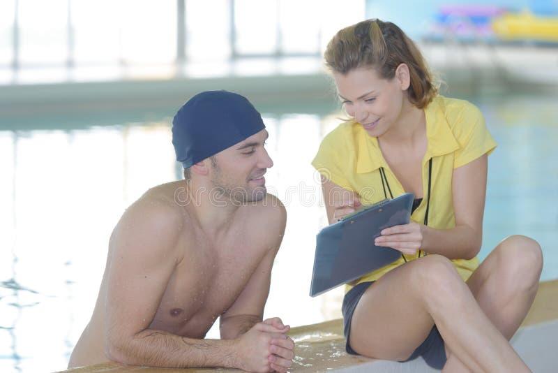 Pływaczka opowiada trenować poolside przy czasu wolnego centrum fotografia stock