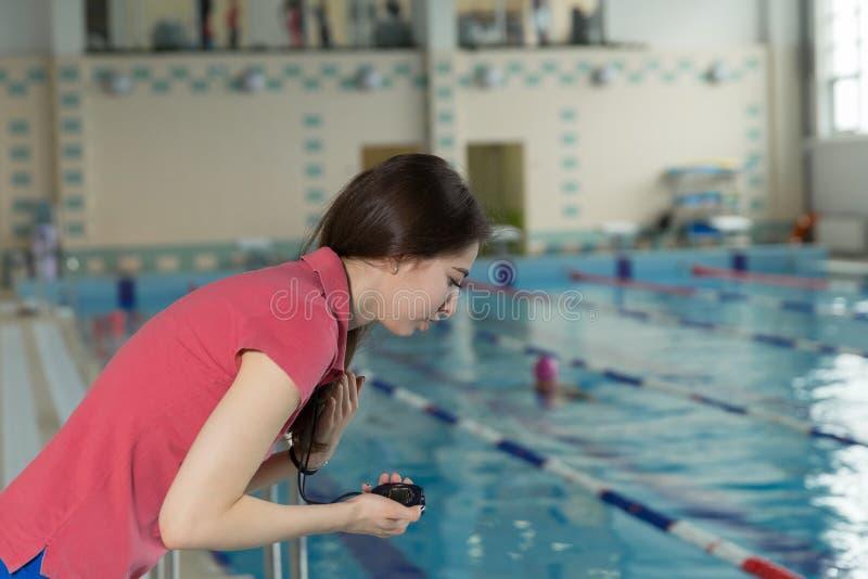 Pływania powozowy patrzeje stopwatch blisko poolside przy czasu wolnego centrum obraz royalty free