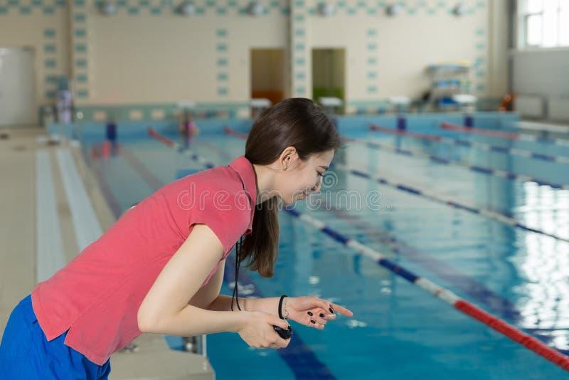 Pływania powozowy patrzeje stopwatch blisko poolside przy czasu wolnego centrum obrazy stock