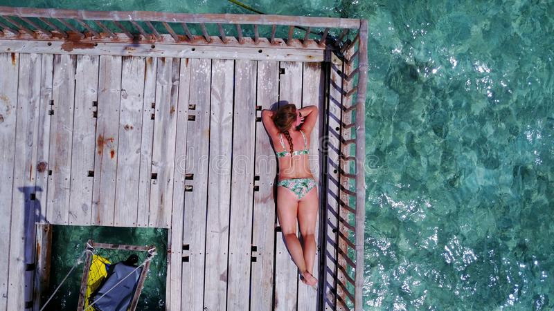 P02003 Aerial flying drone view of Maldives white sandy beach happy young woman relaxing on floating pontoon jetty royalty free stock images