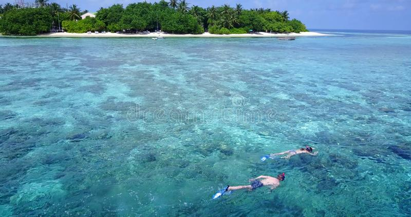 P00069 Aerial flying drone view of Maldives white sandy beach 2 people young couple man woman snorkeling swimming diving on sunny royalty free stock images