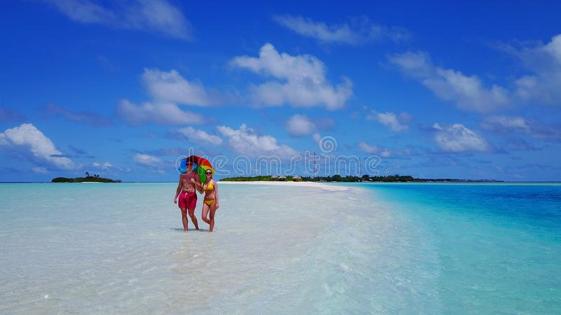 P02585 Aerial flying drone view of Maldives white sandy beach 2 people a young couple man woman walking on sunny. Aerial flying drone view of Maldives white royalty free stock photography