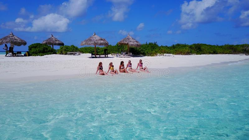 P02159 Aerial flying drone view of Maldives white sandy beach 5 people young woman relaxing sunbathing together on sunny stock images