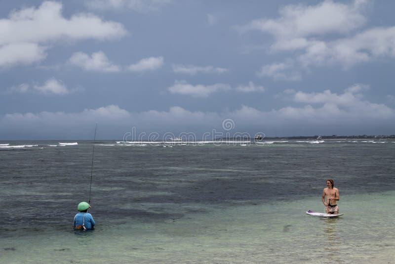 P?cheur et surfers ? la plage de Serangan images libres de droits