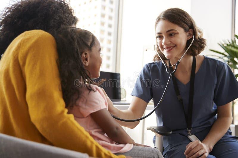 P?diatre f?minin Wearing Scrubs Listening au coffre de filles avec le st?thoscope dans le bureau d'h?pital images libres de droits