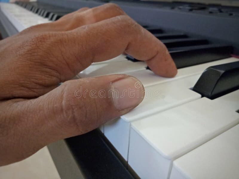 P?e seu dedo sobre o piano para praticar foto de stock