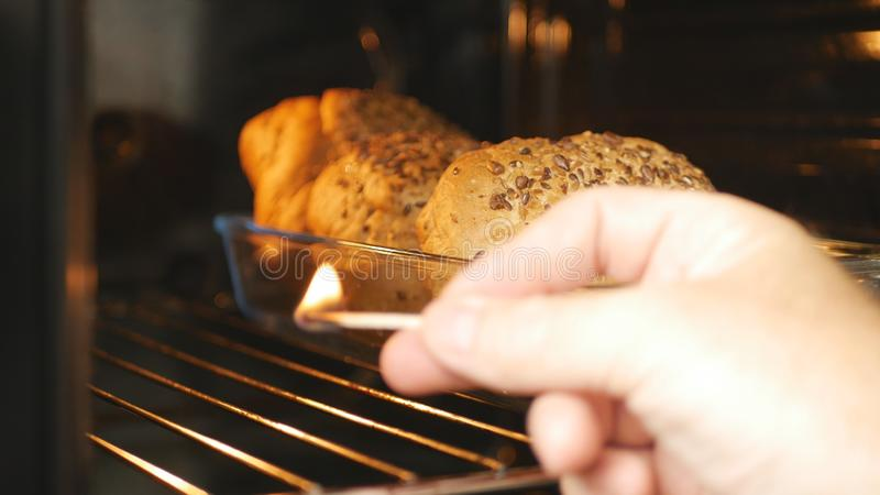 Man in the Kitchen Firing Oven with Matches royalty free stock photos