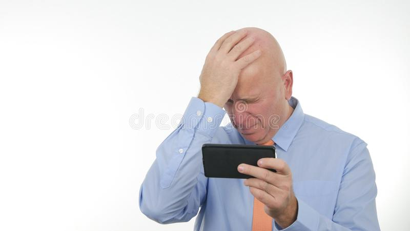 Nervous Businessman make Disappointed Gestures Reading Bad News on Mobile. Concerned upset and Disappointed Businessman make Nervous Gestures Reading Bad News on royalty free stock photo