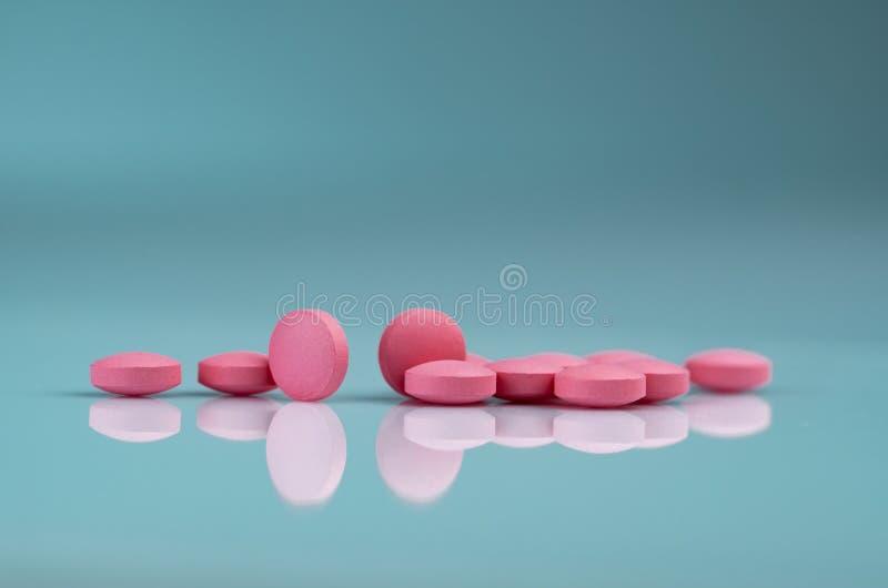 P?ldora rosada redonda de las tabletas en fondo de la pendiente Vitaminas y minerales m?s la vitamina ?cida f?lica E y el cinc en foto de archivo libre de regalías